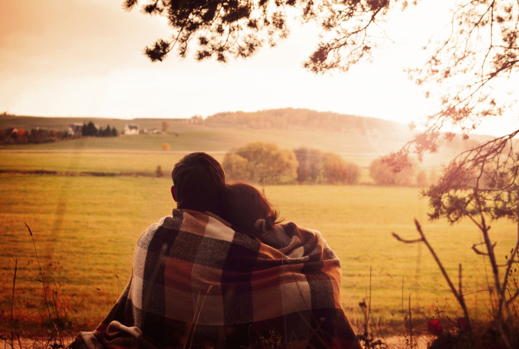 Young couple sitting back having covered with coverlet and enjoy the scenery on the edge of the forest