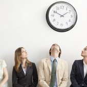 Four business persons sitting on bench looking up at clock.