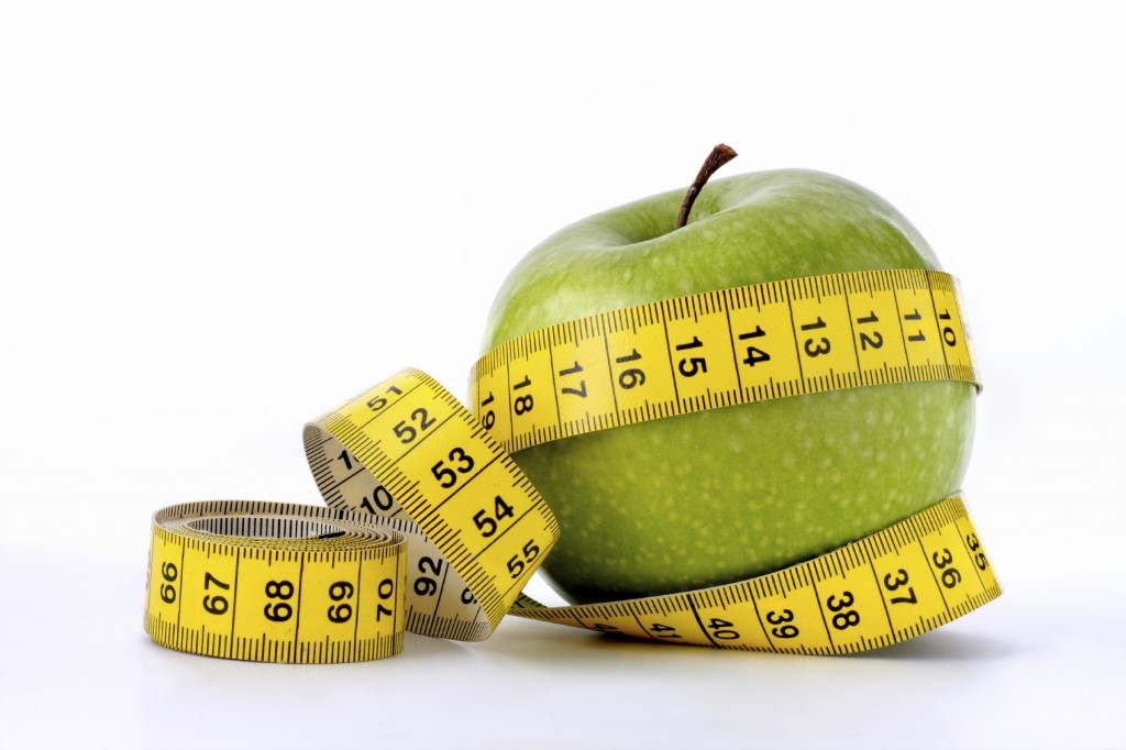 Green apple with measuring tape around it.