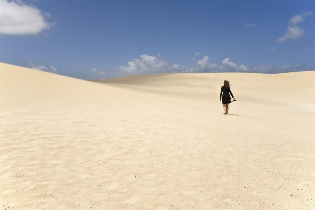 A Girl walking along the dunes