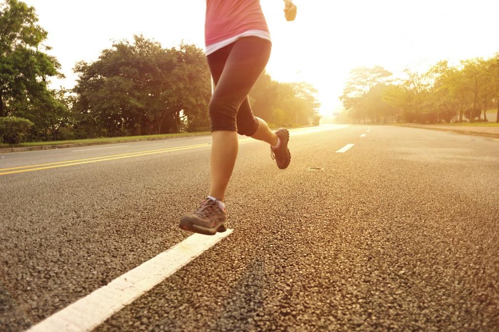 Sportswoman running along driveway