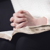 Christian woman pray and folding hands over the holy bible.