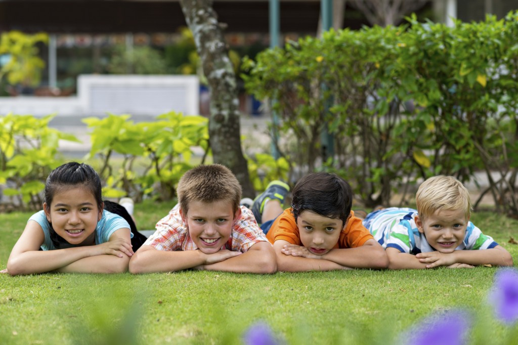 Group of four cheerful kids lying on the stomachs on the grass in the park