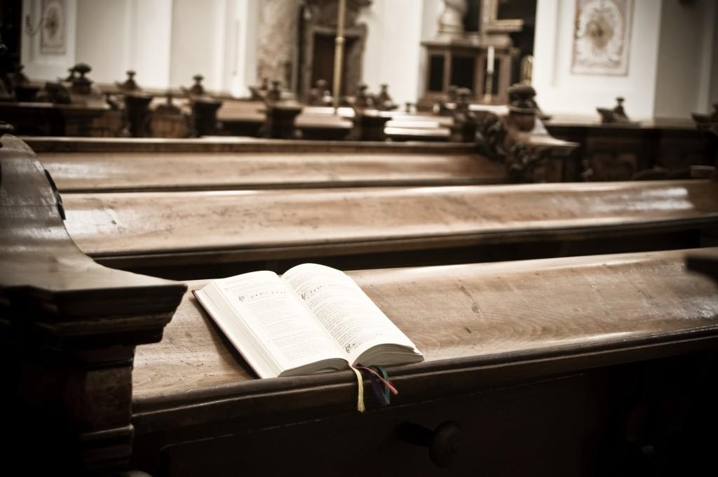 a hymnal sitting on a church pew.