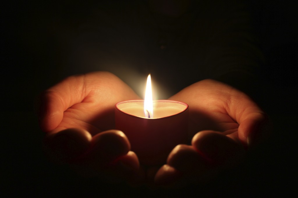 hands holding one candle in darkness