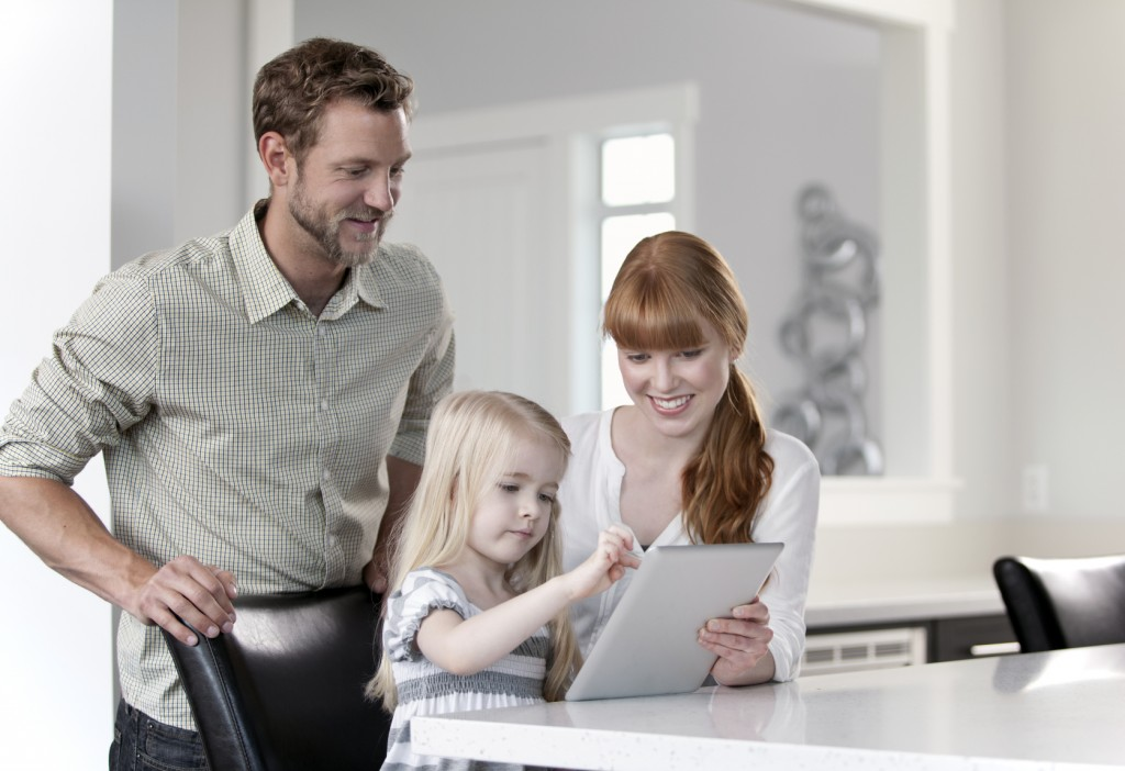 Family of three looking at a digital tablet