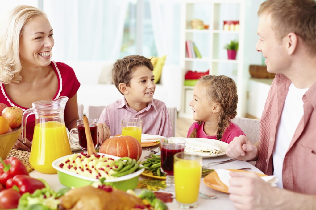 happy family of four sitting at festive table and communicating