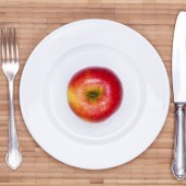 Juicy red apple on the white plate with vintage wooden table background