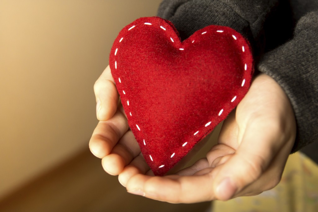 Red heart in child hands, gift