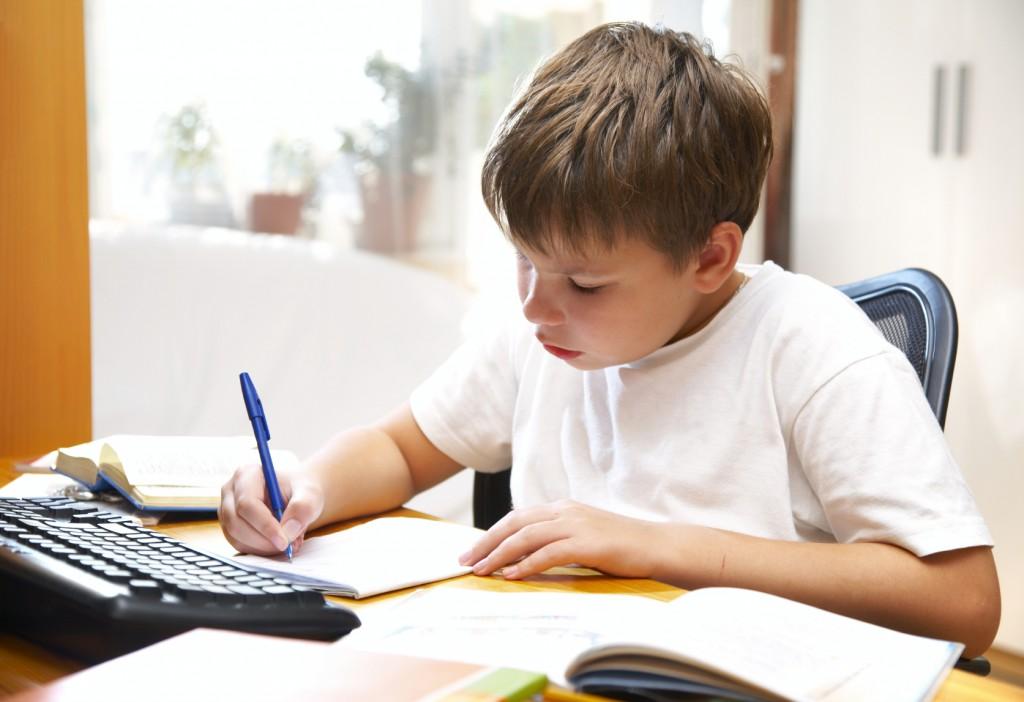 a boy writing at a desk
