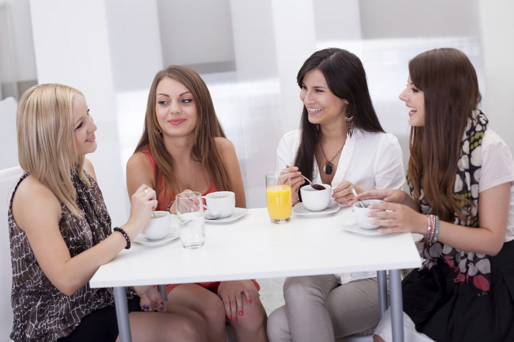 Four female friends seated at a table chatting over coffee