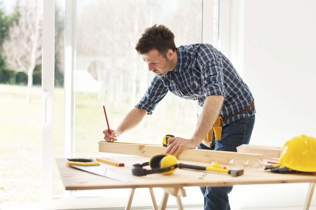 man measuring wooden planks