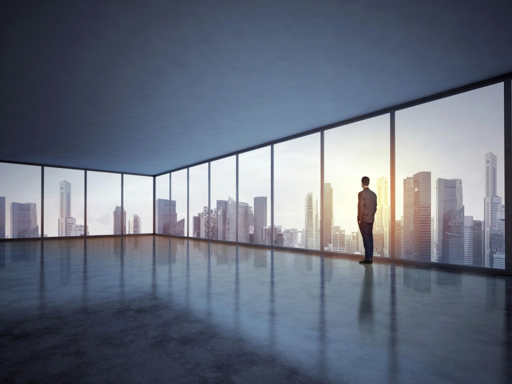 Business man looking megalopolis through window