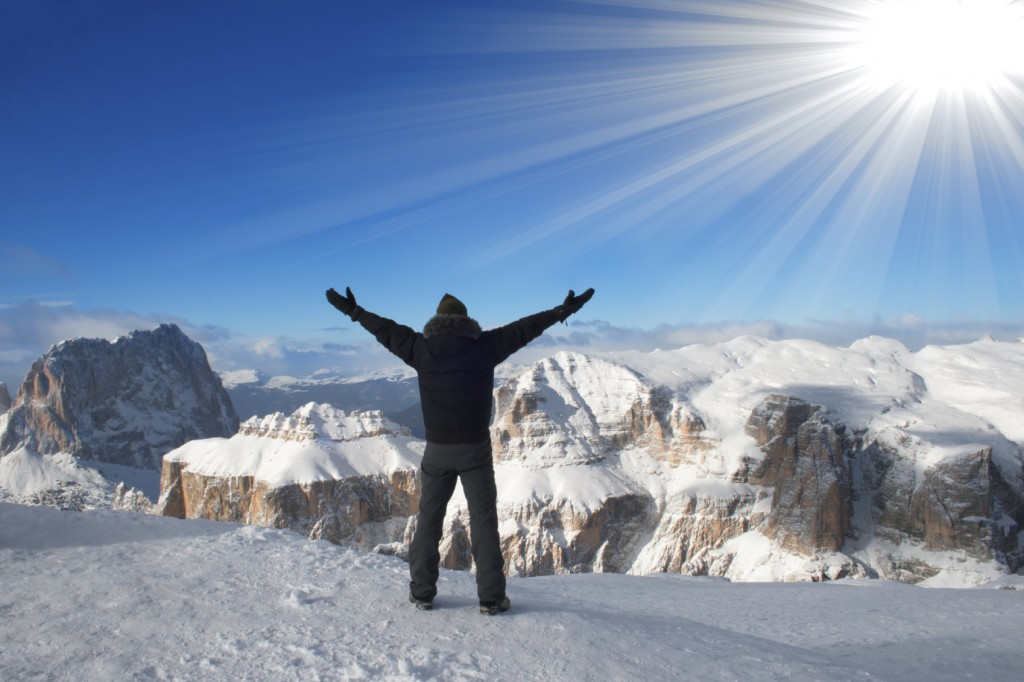 A man triumphantly raising his hands over his head watching the beautiful view of snow-capped mountains