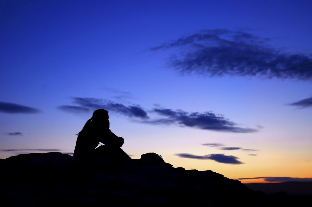 A person meditating and admiring a beautiful sunset or dusk