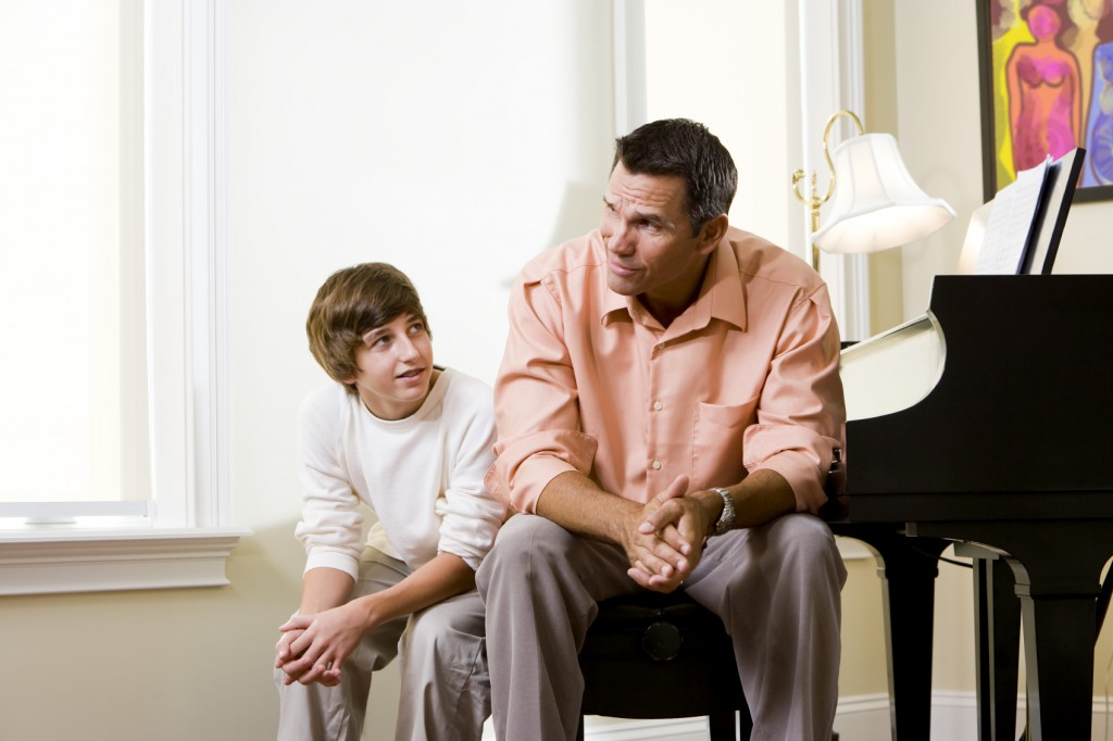Father with teenage son sitting together at home conversing