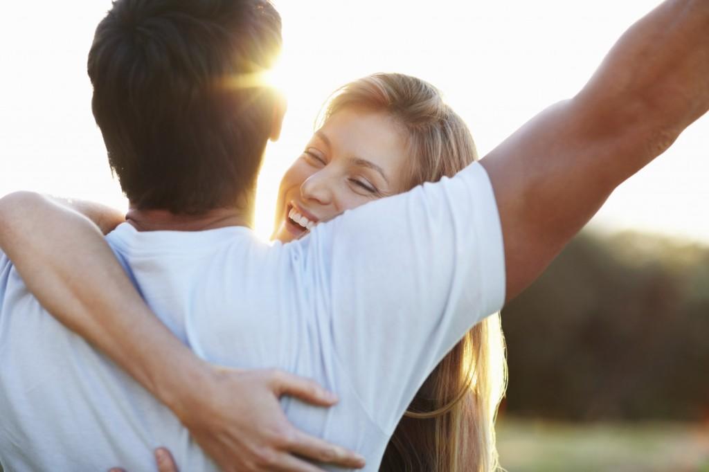 happy woman hugging man outdoors