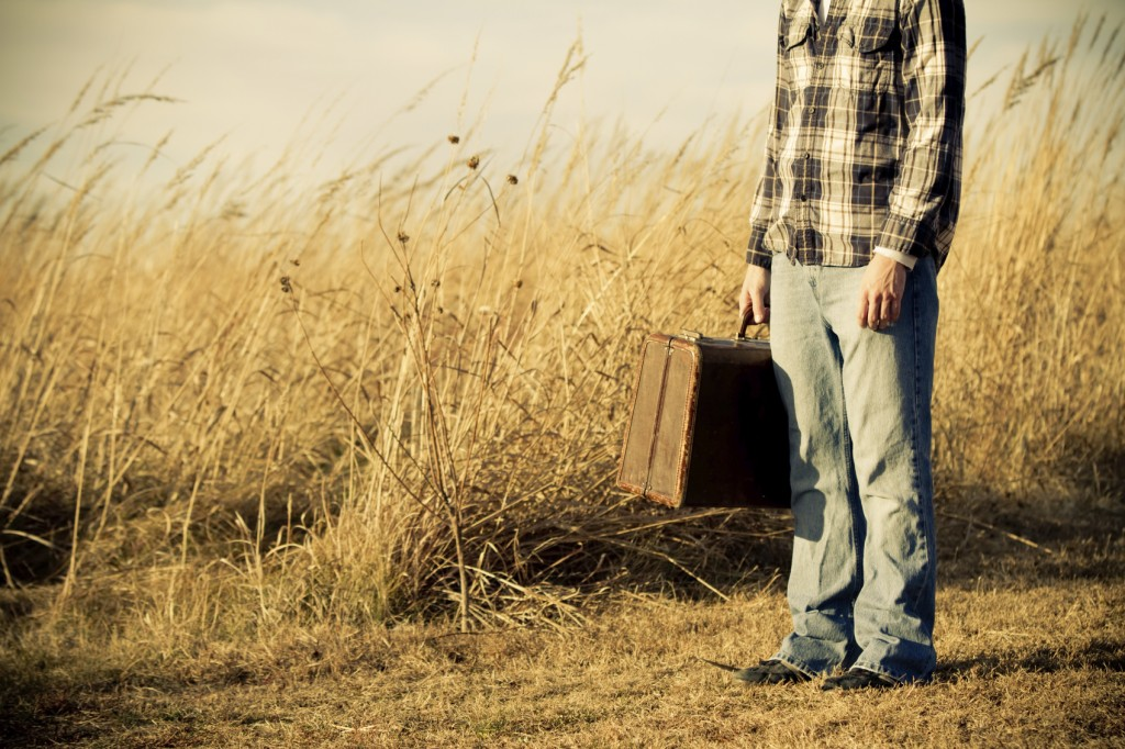 oung man holding his suitcase ready to leave home