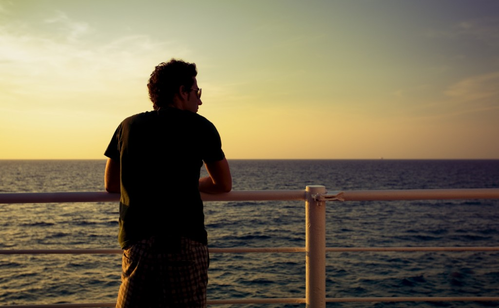 guy standing on a boat and looking at the sea