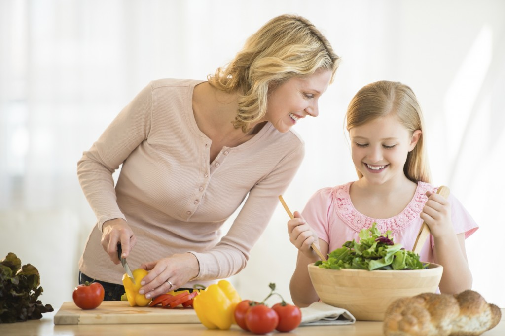 Happy little girl assisting mother in preparing food at kitchen counter