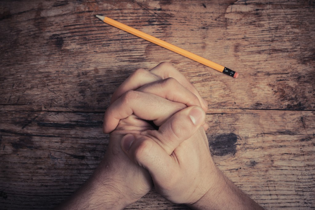 Hands folded in prayer on table with pencil