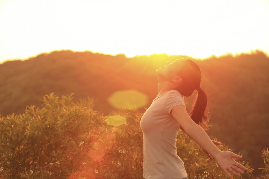 woman with open arms to sunrise