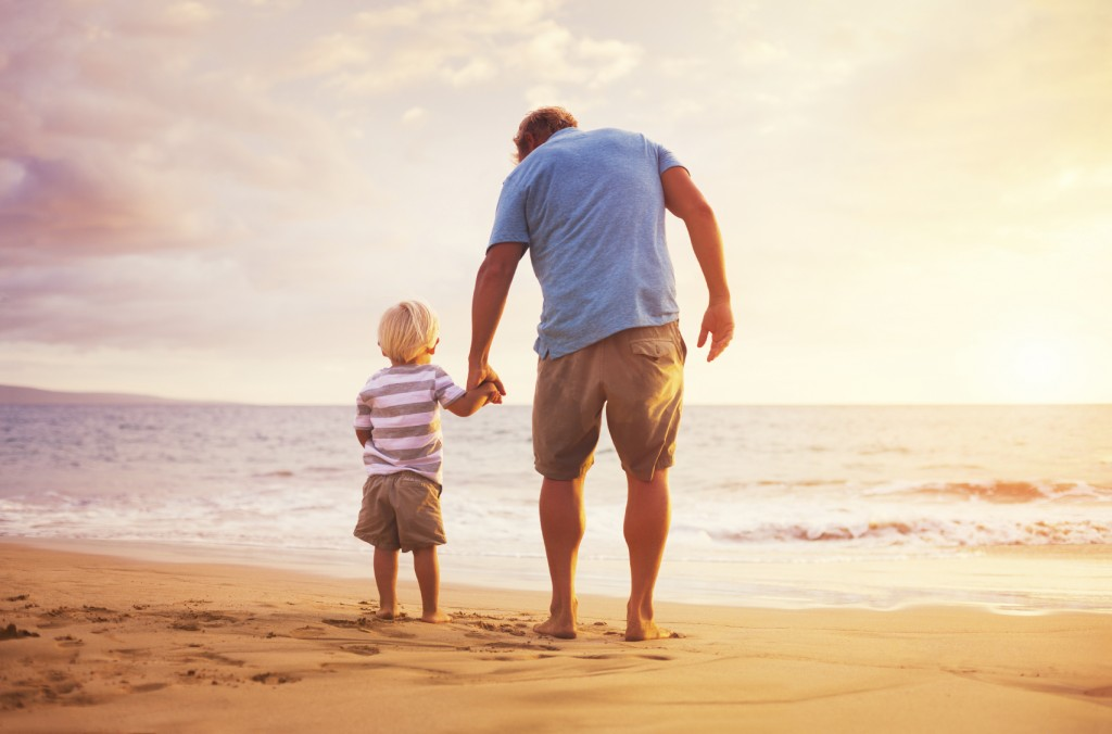 Father and son standing on the sea shore holding hands at sunset
