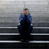 Young man lost in depression sitting on ground street concrete stairs