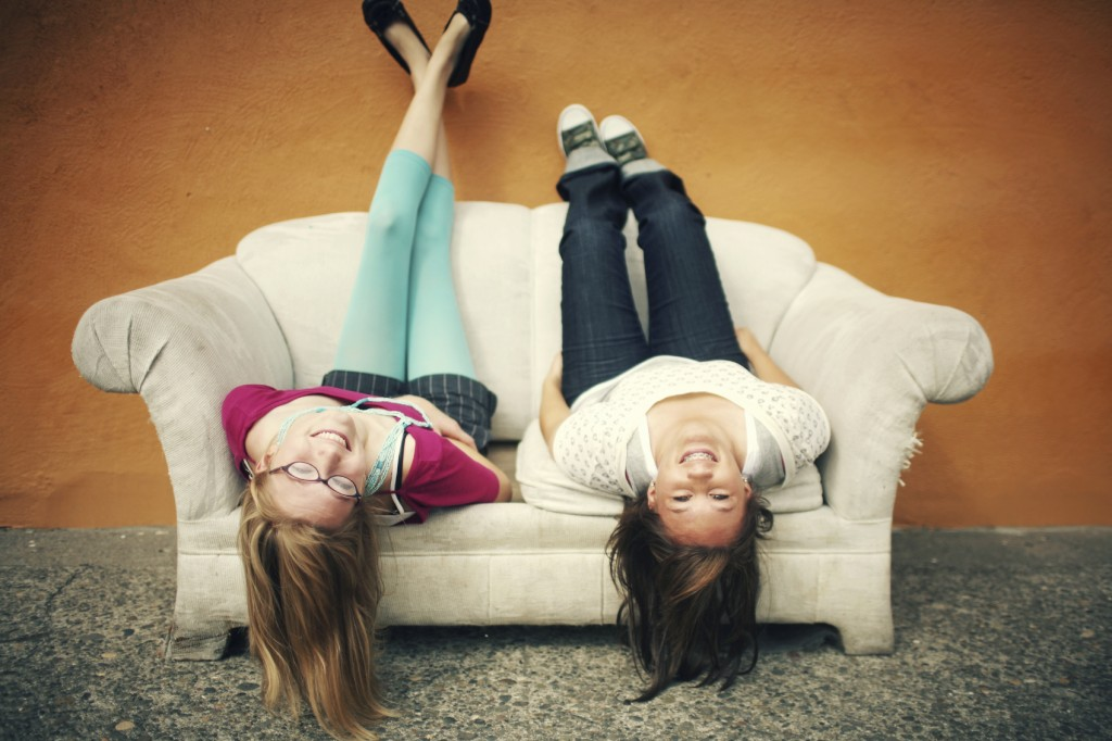 Teen Girls Upside Down on Orange Wall Couch