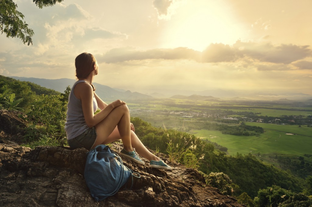 A girl sits on the edge of the cliff and looking at the sun vall