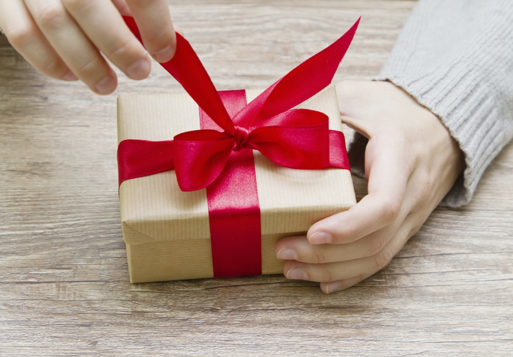 gift box tied with a red ribbon in the hands