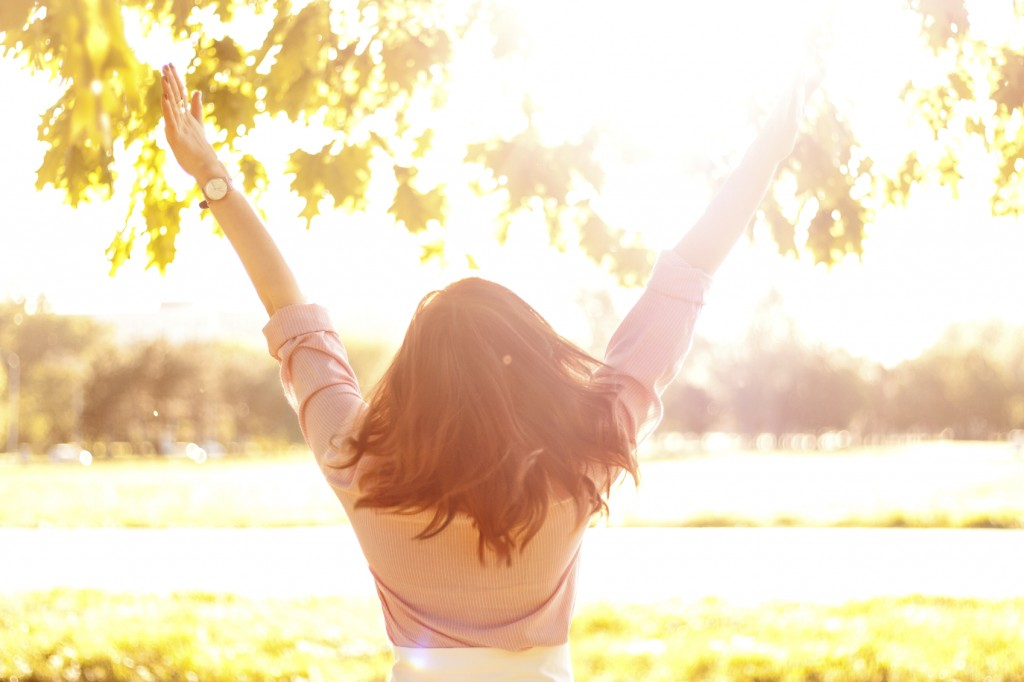 Woman standing in sunlight with arms up