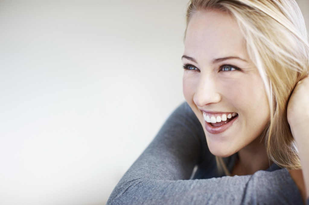 Closeup of attractive young woman smiling while looking at away