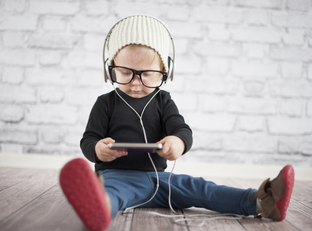 Kid sitting on the floor listening to headphones