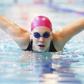 young woman swims the butterfly