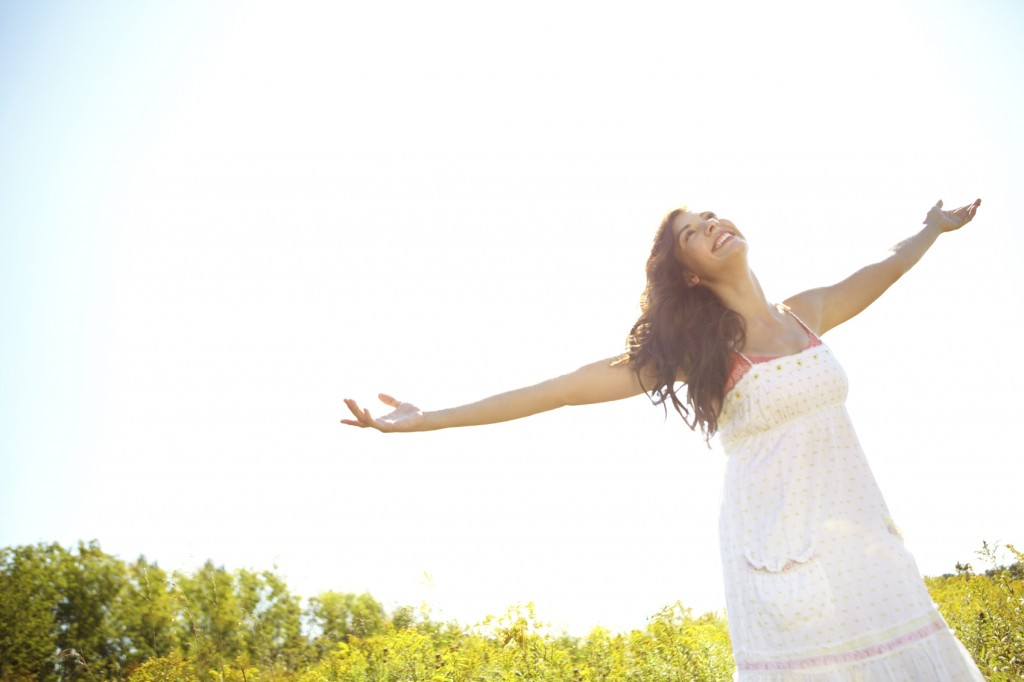 Beautiful young woman with her arms outstretched on a sunny summer's day