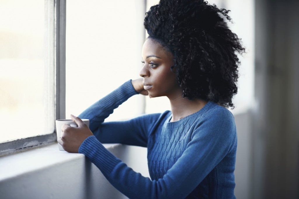 Beautiful african female holding a hot beverage while looking out a window
