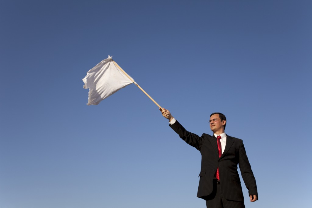 businessman asking for surrending with a white flag