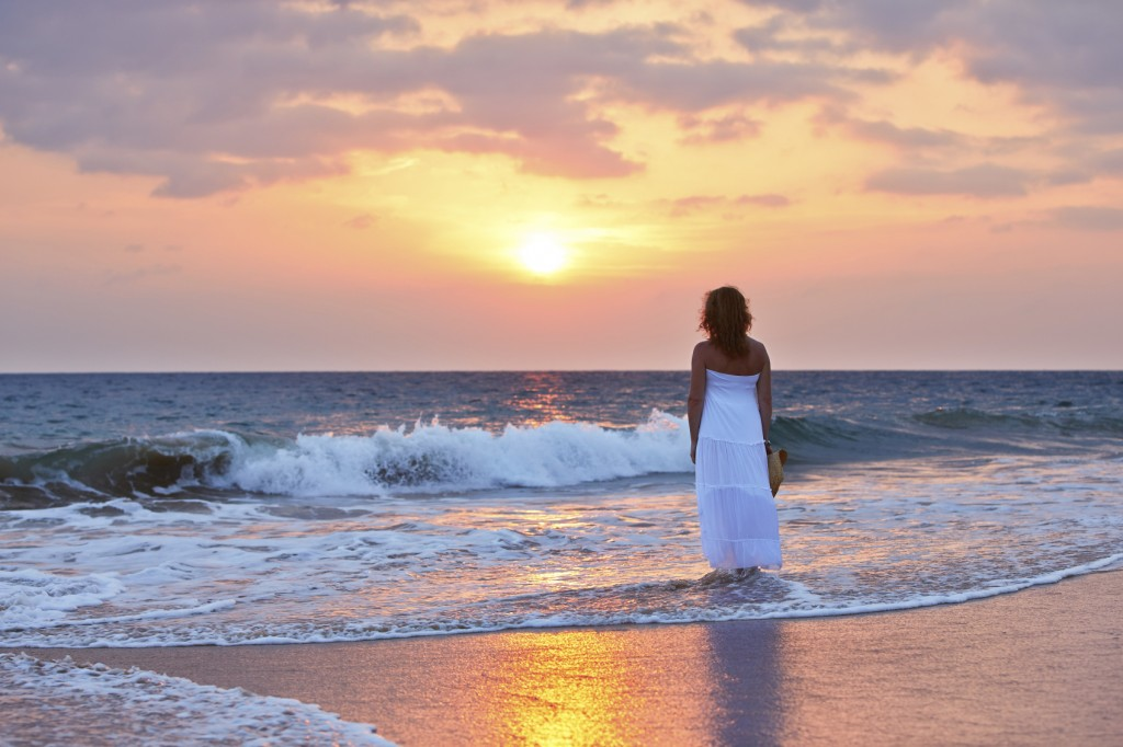 Pretty woman at sunset on the beach.