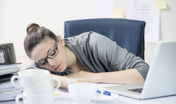 woman snoozing at work, surrounded by coffee cups