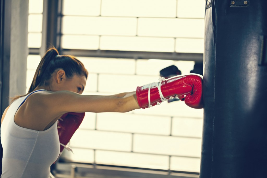 a Female Punching A Bag With Boxing Gloves On