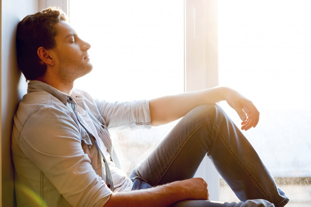 Total relaxation. Side view of handsome young man sitting at the window sill and keeping eyes closed