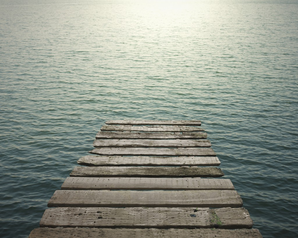 Old wooden pier to the sea with sunlight