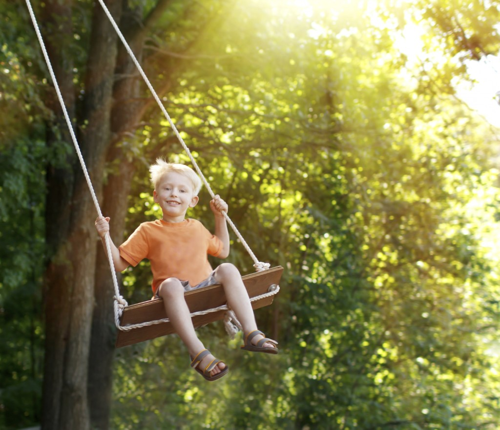 Childhood.Kid on swing.Looking fresh and happy