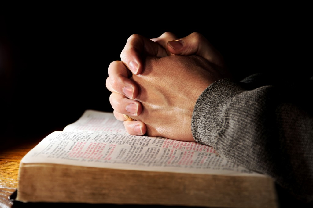 Hands of a man praying in solitude with his Bible