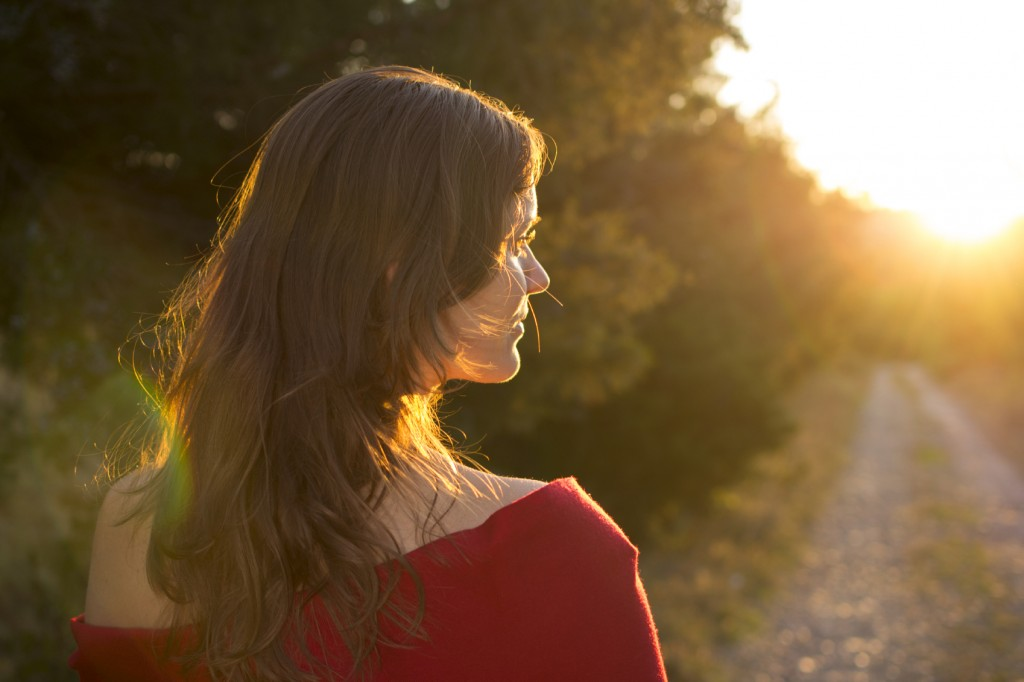 Beautiful young girl walking on a country road towards the light of the setting sun