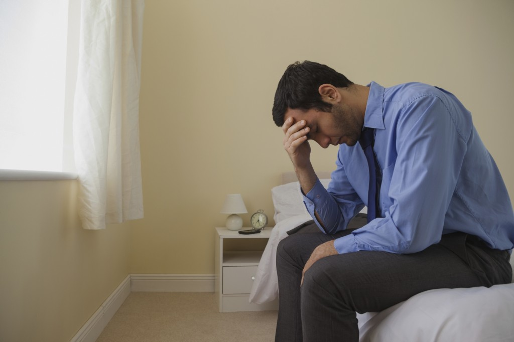 Mournful man sitting head in hands on his bed in a bedroom at home