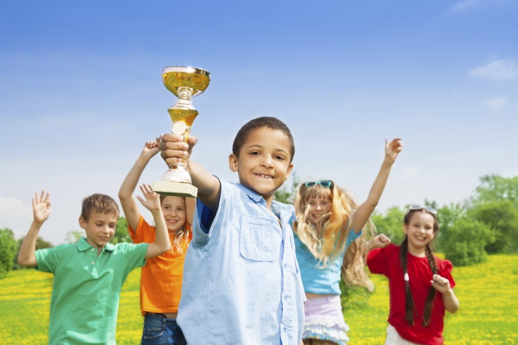 Portrait of black happy smiling little boy holding prize cup with his team on background