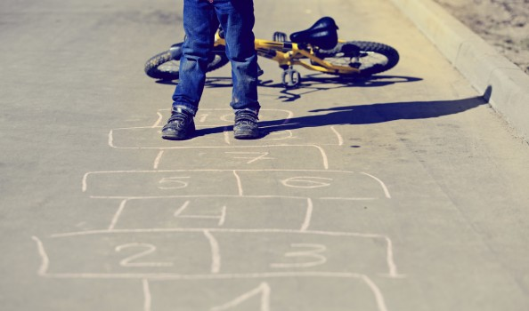 little boy playing hopscotch