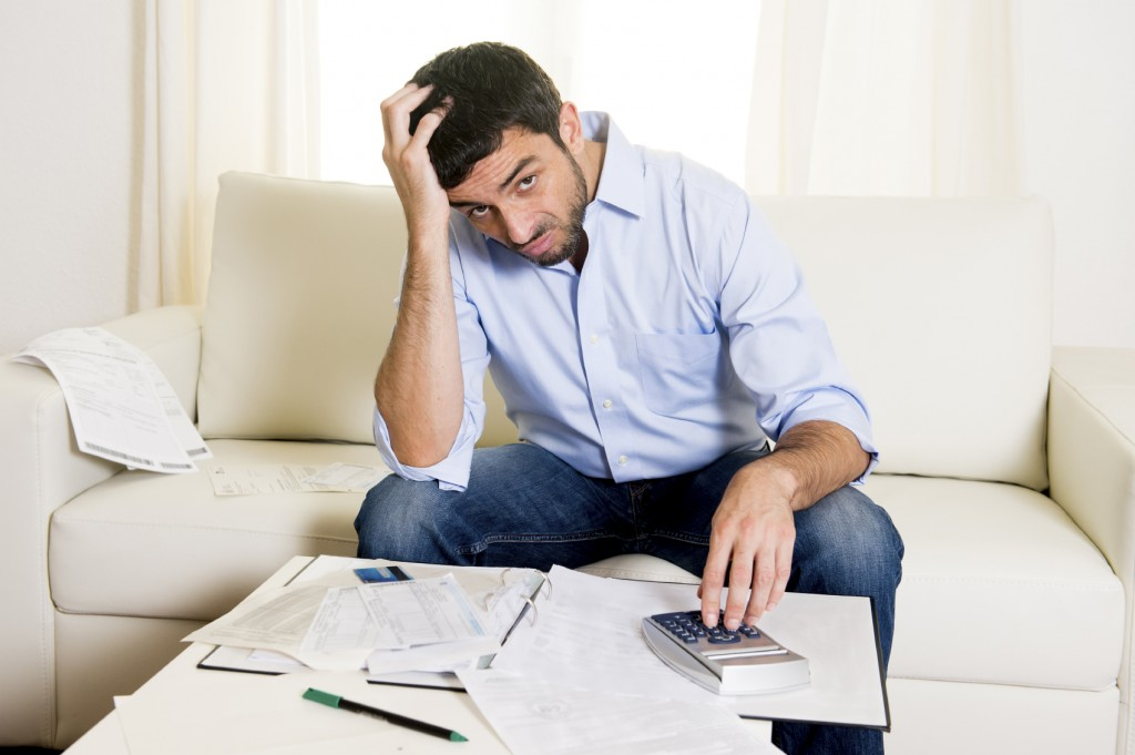 business man worried paying bills on couch